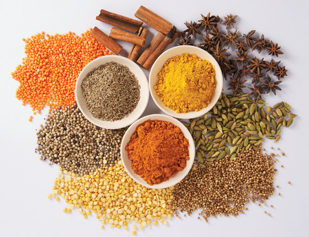 dried food: A close-up of spices in little bowls, on white background.