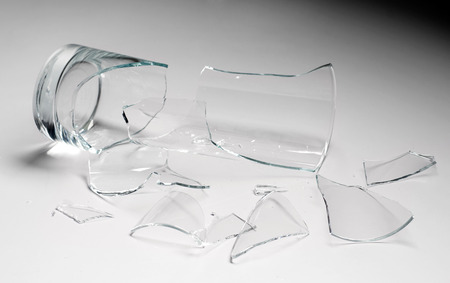 shattered glass: broken glass against grey background, concept of danger Stock Photo