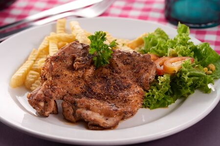 grilled chicken chop served with potato fries and salad.