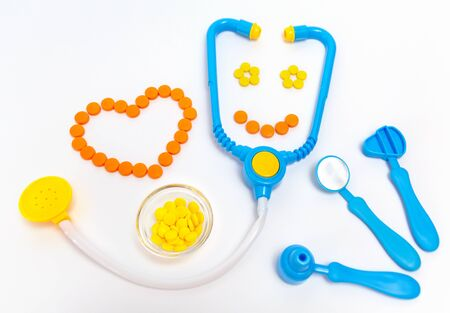 Medicine concept. Childrens toys by doctor. A heart is by orange pills. Stok Fotoğraf
