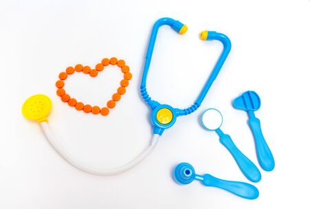 Medicine concept. Childrens toys by doctor. A heart is by orange pills. Stock Photo