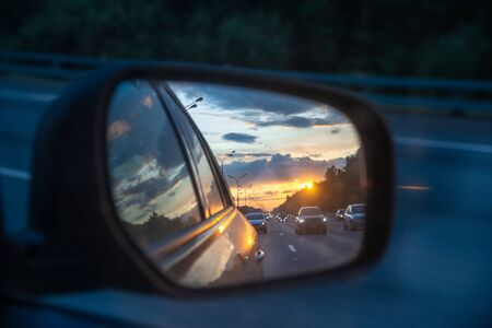 Sunset and beautiful sky is reflected in the mirror of a car. Cars drive along a high road in the evening. Theme of travel by car Banco de Imagens
