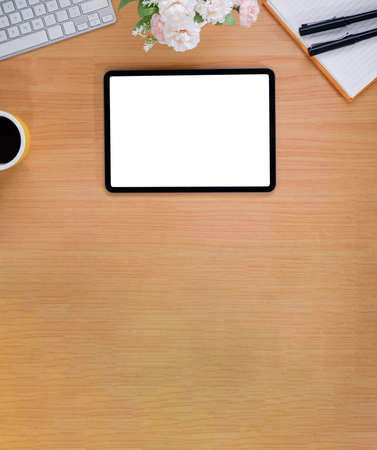 Top view of simple workspace with mock-up tablet, computer device and copy space on wooden table background