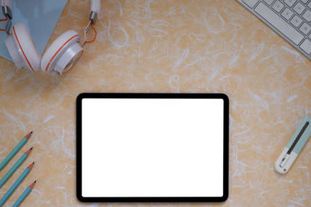 Top view image of white blanks screen computer tablet with putting on colorful working desk and surrounded by pen, key borde, headphoned.Orderly workspace concept.