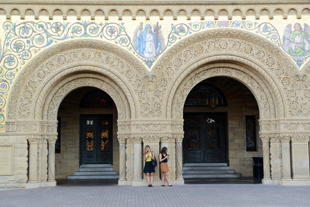 Two women texting on the phone in front of Stanford Memorial Church