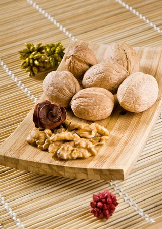 Walnut fruits on wooden dish. Juglans. Archivio Fotografico