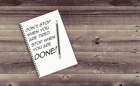 positive note: Inspirational quote on notepad. DONT STOP WHEN YOU ARE TIRED. STOP WHEN YOU ARE DONE! Stock Photo
