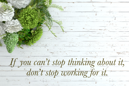 Inspirational quote on wooden table. If you can�t stop thinking about it, don�t stop working for it. Stock Photo