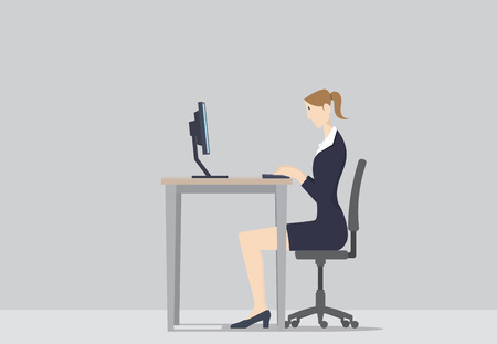 A woman working at her office desk, in front of computer.
