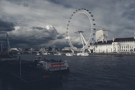 nicknamed: London,Uk - April 15, 2016:  View of Thames river with cruise tour boats near the giant Ferris wheel nicknamed London Eye.