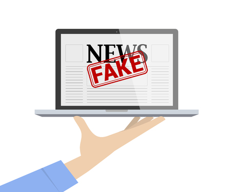 Hand holding laptop showing fake news website. Provide fake news concept.