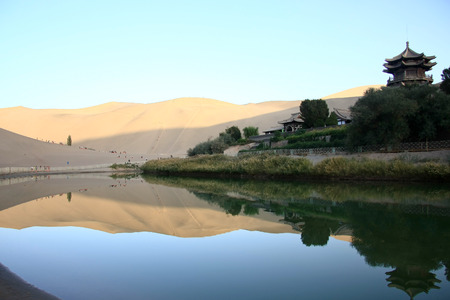 """crescent lake: Mingsha, located in the southern suburbs of Dunhuang City, Gansu Province, due to the sand moving sound derived from the name of Dunhuang """"Eight."""" Crescent Lake, surrounded by Mingsha, because the water resembles a crescent named. Stock Photo"""