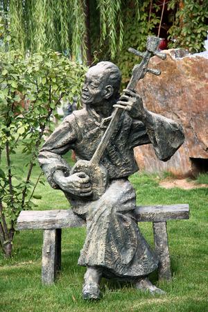 waterwheel: Statue of a man playing instrument, Waterwheel Park Lanzhou