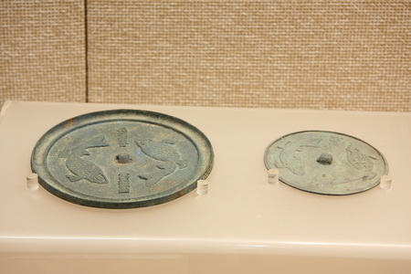 """wen: Left: Pisces pattern bronze mirrors (Song). Right: """"The Feast"""" Wen Ming bronze mirrors Pisces (Ming), collections in Huzhou, Zhejiang Museum."""