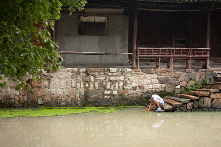 villager: Villager washing at the river in Jiangnan water town Editorial