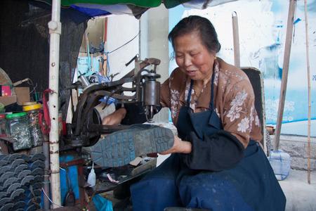 alte dame: eine alte Dame, die Reparatur der Schuhe