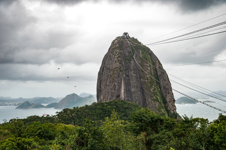 climbing cable: Cableway to Sugarloaf Mountain in Rio de Janeiro, Brazil under stormy rain clouds with  heavy sky Stock Photo