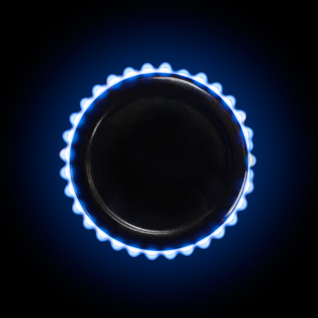 stove top: burning gas stove  top with blue flames in the dark on a black background