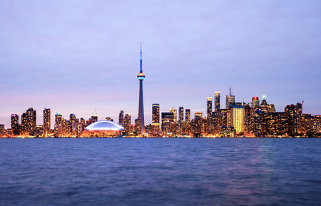 building cn tower: Panorama of Toronto skyline at night with CN Tower over lake from Central Island