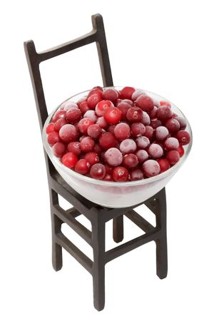 bacca: Red fresh cranberry in glass bowl and black chair. Isolated on the white background. Stock Photo
