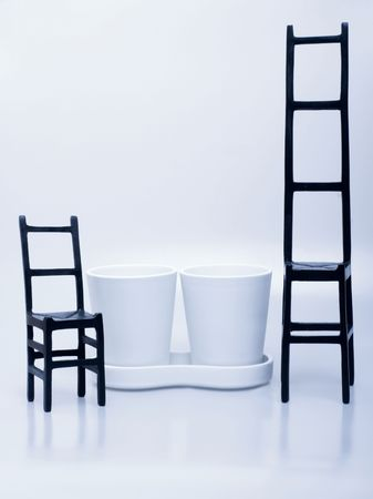 Set of plant pots and two black chairs Stock Photo