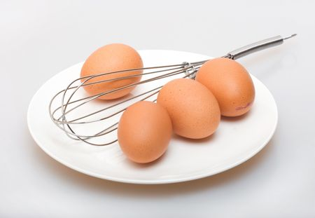 Eggs on a white plate and whisk