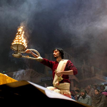 uttar: VARANASI INDIA JANUARY 14 2010: Hindu priests conducts religious Ganga Maha Aarti ritual fire puja at Dashashwamedh Ghat in Varanasi Uttar Pradesh India Editorial