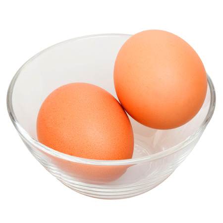 Two raw eggs in glass bowl isolated on the white background photo