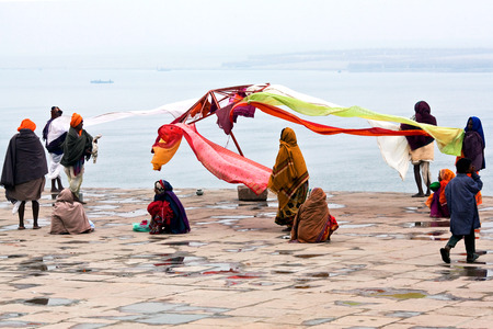 neighbours: Indian women dry their saris at Dashashwamedh ghat after bathing in the sacred Ganges river on January 13 2010 in Varanasi State of Uttar Pradesh India Editorial