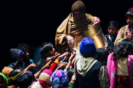 benares: VARANASI, UTTAR PRADESH, INDIA  - JANUARY 15: Hindu man offered prasad to poor people after Ganga Maha Aarti ceremony at Dashashwamedh Ghat on January 15, 2010 in Varanasi, India