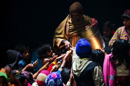 benares: VARANASI, UTTAR PRADESH, INDUA  - JANUARY 15: Hindu man offered prasad to poor people after Ganga Maha Aarti ceremony at Dashashwamedh Ghat on January 15, 2010 in Varanasi, India Editorial