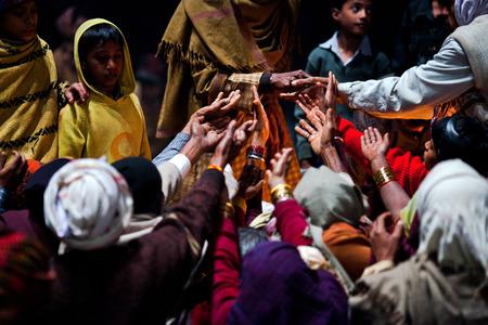 varanasi: VARANASI, UTTAR PRADESH, INDIA  - JANUARY 15: Hindu man offered prasad to poor people after Ganga Maha Aarti ceremony at Dashashwamedh Ghat on January 15, 2010 in Varanasi, India