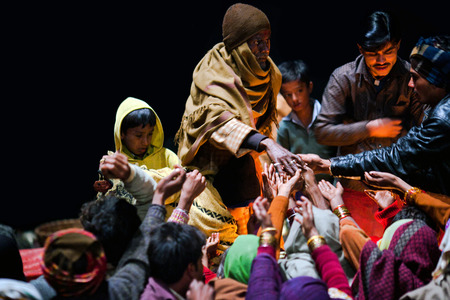 uttar: VARANASI, UTTAR PRADESH, INDIA  - JANUARY 15: Hindu man offered prasad to poor people after Ganga Maha Aarti ceremony at Dashashwamedh Ghat on January 15, 2010 in Varanasi, India