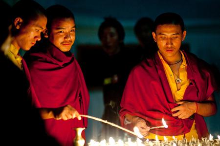KATHMANDU, NEPAL - MARCH 25: Unidentified buddhist monks lighting candles before prayer at Boudhanath Stupa on March 25, 2010 in Kathmandu, Nepal