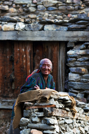 pauper: ANNAPURNA CIRCUIT, NEPAL - APRIL 23: Old tibetian woman from the village of tibetan refugees on the doorstep of his homel in the Himalayas, Nepal on 23 April 2008.