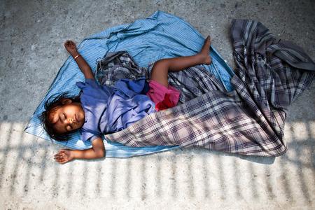 penury: KATHMANDU, NEPAL - APRIL 06: A little Nepalese boy sleeping on the street on April 6, 2010 in Kathmandu, Nepal.