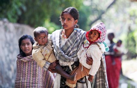 niños pobres: KATMANDU, NEPAL - 08 de noviembre: Mujer nepalesa con dos hijos pide dinero en la calle en Katmandú, Nepal, el 8 de noviembre, 2009.