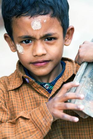 penury: KATHMANDU, NEPAL - NOVEMBER 14: Nepalese boy carrying bricks at building site in Kathmandu, Nepal on November 14, 2009. Editorial