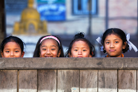 little girl child: BHAKTAPUR, NEPAL - JANUARY 8: Nepalese schoolgirls poses for a photo during their break time on January 8, 2010 in Bhaktapur, Kathmandu Valley, Nepal