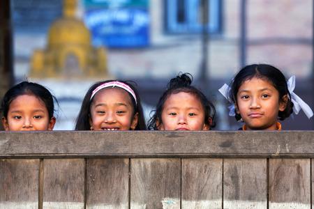 poor: BHAKTAPUR, NEPAL - JANUARY 8: Nepalese schoolgirls poses for a photo during their break time on January 8, 2010 in Bhaktapur, Kathmandu Valley, Nepal