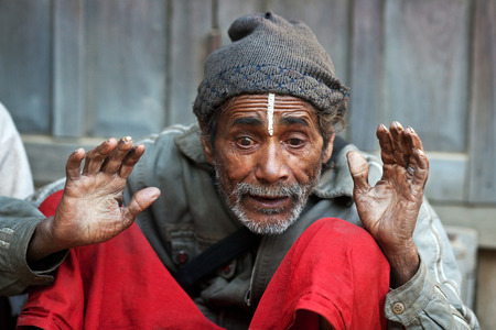 destitution: KATHMANDU, NEPAL - JANUARY 08, 2010: Nepalese man seeking alms on the street