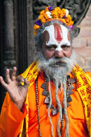 seeks: KATHMANDU - NOVEMBER 14: Shaiva sadhu (holy man) seeks alms in front of a temple on November 14, 2009 in Kathmandu, Nepal