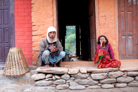 pauper: MANASLU AREA, NEPAL - NOVEMBER 15: Old Gorkhas man and woman on the doorstep of their home on November 15, 2009 in Arughat, Gorkha District, Nepal.
