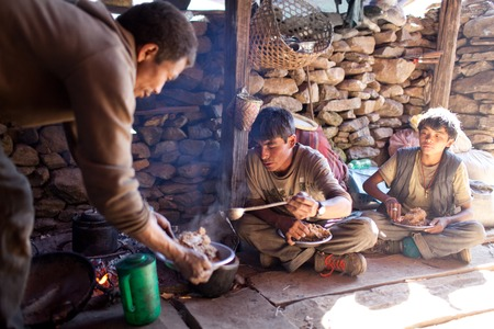 penury: MANASLU AREA, NEPAL - NOVEMBER 20: Nepalese porters eating porrige dhindo national tibetan dish on November 20, 2009 in Gorkha District, Nepal.