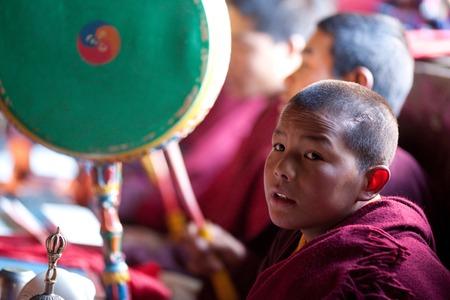 monk: LHO, GORKHA, NEPAL - NOVEMBER 28: Buddhist monk Lhakpa Dorje, 9, poses for a photo during puja ceremony in Lho monastery on November 28, 2009 in Manaslu conservation area, Nepal.