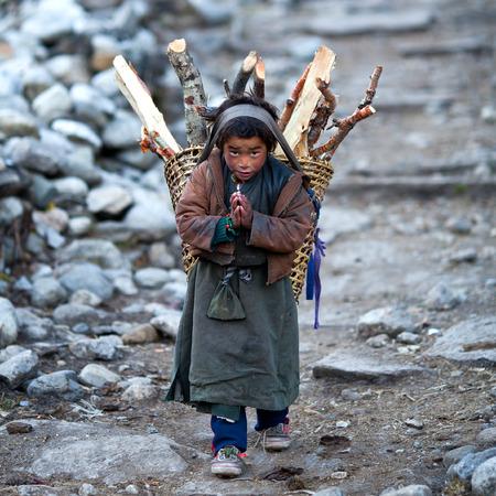 LHO, GORKHA, NEPAL - NOVEMBER 29: Tibetan boy with basket of firewood poses for a photo on the road to Lho village on November 29, 2009 in Gorkha District, Nepal