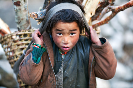 pauper: LHO, GORKHA, NEPAL - NOVEMBER 29: Tibetan boy with basket of firewood poses for a photo on the road to Lho village on November 29, 2009 in Gorkha District, Nepal