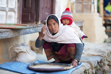 illiterate: MANASLU AREA, NEPAL - DECEMBER 06: Peasant woman in national clothes with baby from gorkhas village on December 06, 2009 in Gorkha District, Nepal Editorial