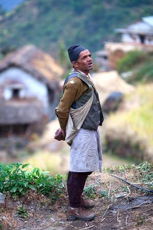 penury: GHANDRUK, ANNAPURNA CONSERVATION AREA, NEPAL - DECEMBER 09: Gurung man in national clothes standing on the hill on December 09, 2009 in Ghandruk, Nepal. Ghandruk is a biggest village of gurungs.