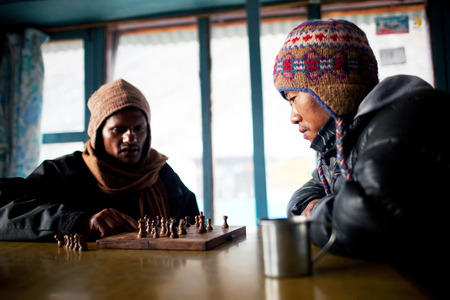 dinner hall: ANNAPURNA BASE CAMP, NEPAL - DECEMBER 14: Nepalese porters thinks over the chessboard in dinner hall of local guesthouse on December 14, 2009 in Annapurna base camp, Nepal. The Sherpa people of Nepal have established a reputation as mountaineering porters Editorial